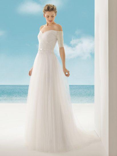Открытое свадебное платье с силуэтом «принцесса» притягивает взгляды роскошным портретным декольте, дополненным романтичными полупрозрачными рукавами, украшенными горизонтальными драпировками по всей длине. Корсет в форме сердца также украшают драпировки, а в области талии его декорирует широкая полоса кружева, служащая подкладкой для узкого атласного пояса.