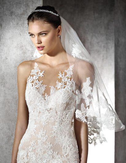 Свадебное платье силуэта «русалка» с длинным шлейфом и кружевом на бежевой подкладке.