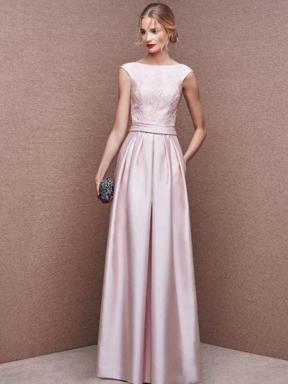 Розовое вечернее платье из глянцевой атласной ткани, красиво очерчивающее шею округлым вырезом, дополненным широкими бретелями, чуть спущенными с плеч.  На корсете в качестве отделки располагается кружевной рисунок.  Талию помогает выделить широкий атласный пояс.  Юбку прямого силуэта украшают выразительные вертикальные складки, спускающиеся по всей длине подола, и скрытые карманы по бокам.  Спинка украшена глубоким округлым вырезом.