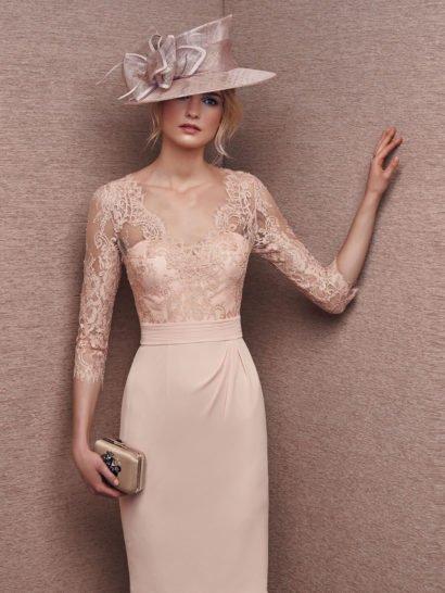 Романтичное вечернее платье длиной до колена выполнено из нежной розовой ткани с мягким глянцевым блеском. Кружевная отделка, подобранная в тон, дополняет открытый лиф в форме сердечка, создавая V-образный вырез с фигурным краем и прямого кроя рукава длиной чуть ниже локтя. На талии – широкий пояс с отделкой из декоративных горизонтальных швов, от него на юбку прямого кроя спускаются изящные драпировки.