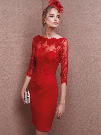Короткое вечернее платье насыщенного красного цвета с декором из полупрозрачной кружевной ткани в тон. Кружево закрывает лиф в форме сердечка, создавая портретный вырез с фигурным краем и рукава длиной до локтя с ажурными манжетами. На спинке ажурная ткань нежно обрамляет округлый вырез. Выделить линию талии помогает широкий пояс, украшенный несколькими горизонтальными швами. От талии спускается сдержанная юбка без декора.