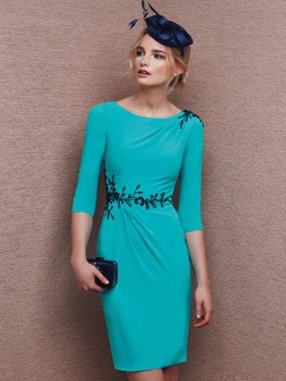Голубое вечернее платье женственно обрисовывает фигуру силуэтом «футляр», с округлым вырезом декольте, вырезом такой же формы на спинке платья и рукавами прямого кроя длиной чуть ниже локтя. Изящные драпировки на уровне естественной линии талии и на плече дополняют лаконичный силуэт. Их направление помогает подчеркнуть романтичная цветочная вышивка, выполненная контрастной черной нитью и бисером на талии и у выреза.