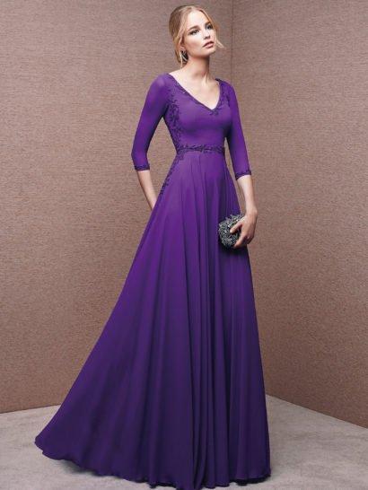 Женственное вечернее платье с юбкой А-силуэта, изысканно струящейся мягкими волнами шифона от линии талии по всей длине подола.  Глубокое V-образное декольте с облегающими рукавами длиной в три четверти стильно выделяет фигуру.  В качестве отделки лаконичного образа использована вышивка бисером в цвет ткани, нежный цветочный рисунок которой узкими полосами очерчивает линию талии, спускается по бокам платья и обрисовывает манжеты.