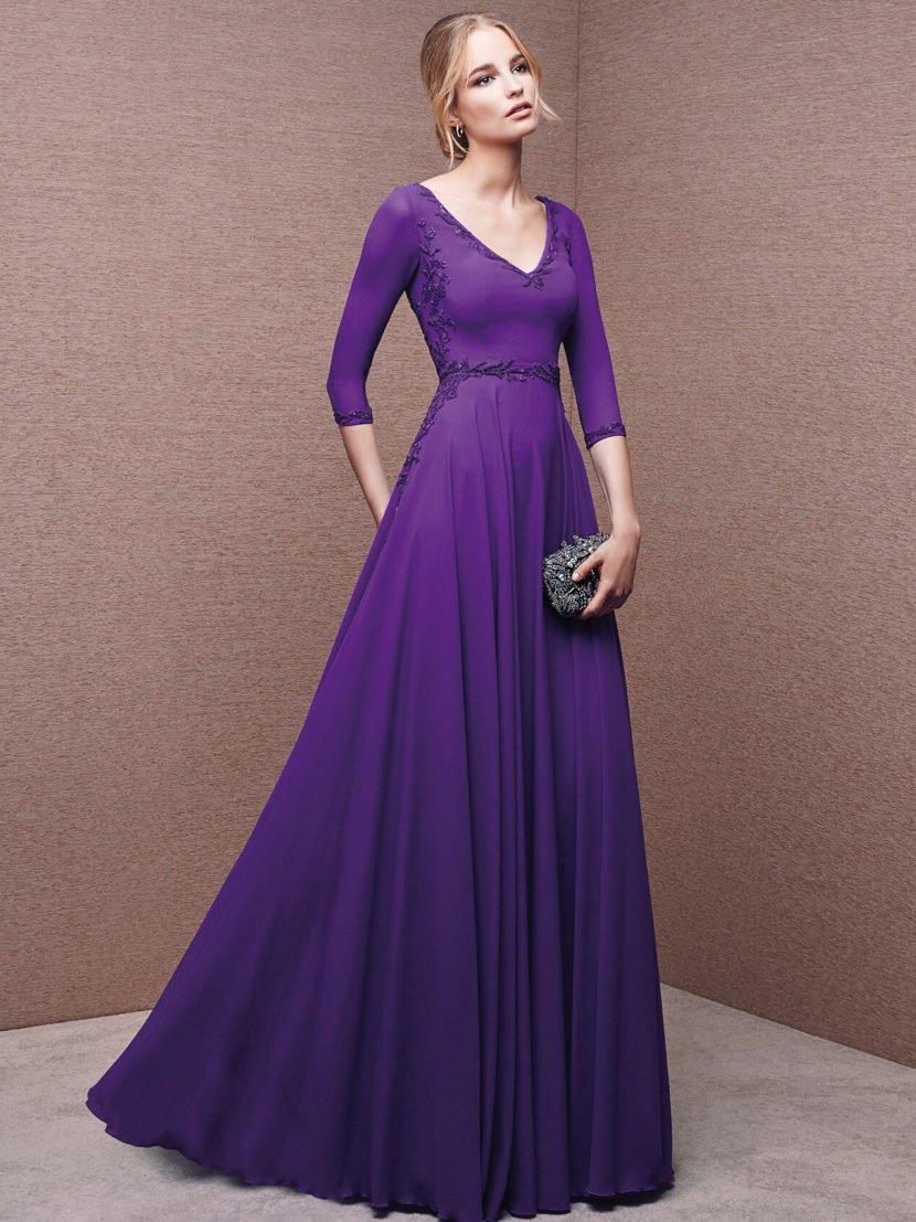 Вечернее платье максимальной длины с рукавами три четверти и лифом с V-образным вырезом.