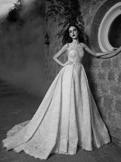 Торжественное свадебное платье с пышной юбкой, облегающее силуэт изысканным закрытым лифом с округлым вырезом, оформленным полупрозрачной ажурной тканью. На спинке та же ткань обрисовывает округлое декольте.  Кружевная юбка декорирована плотными вертикальными складками ткани, спускающимися от линии талии по всей длине подола, а сзади роскошным завершением образа становится широкий полукруг длинного шлейфа.  Эксклюзивно в салоне Виктория