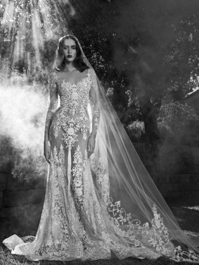 Чувственная красота полупрозрачной ткани с кружевным рисунком в закрытом свадебном платье объединяется со сдержанной простотой прямого силуэта, стильно обрисовывающего каждый изгиб фигуры.  Длинный шлейф, образующий крупные волны ткани, прекрасно вписывается в роскошное настроение образа. Фигурный округлый вырез, оформленный кружевом, дополнен длинными рукавами из прозрачной ткани, также покрытой аппликациями.  Эксклюзивно в салоне Виктория
