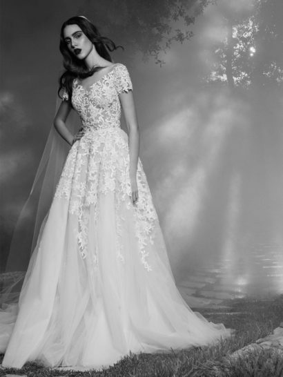 Закрытый крой верха свадебного платья с округлым вырезом под горло и рукавами прямого кроя необычно и стильно сочетается с полупрозрачной тканью, декорированной аппликациями с крупным цветочным рисунком. Такая же отделка покрывает и верхнюю половину пышного многослойного подола, от талии спускающегося вниз крупными складками. Сзади роскошная юбка образует пышный полупрозрачный шлейф.  Свадебное платье 2016 года