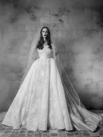 Эксклюзивное свадебное платье от Zuhair Murad открывает декольте стильным лифом прямого кроя, под которым располагается корсет, декорированный кружевными аппликациями и горизонтальными складками фактурной плотной ткани.  Царственная красота юбки обеспечена невероятной пышностью, полупрозрачным верхом с крупными кружевными деталями и роскошными вертикальными складками, а также пышным шлейфом, простирающимся за платьем сзади.  Эксклюзивно в салоне Виктория