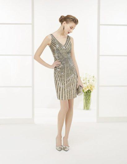 Потрясающее вечернее платье светлого бежевого цвета с облегающим силуэтом «футляр» женственно очерчивает фигуру и обнажает ноги юбкой длиной чуть выше колена. Усиливает впечатление соблазнительный V-образный вырез с узкими симметричными бретелями. Главной изюминкой образа служит отделка, выполненная из золотистых пайеток, располагающихся диагональными полосами по всей длине вечернего платья.