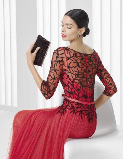Вечернее платье красного цвета с длинным рукавом, украшенное черной бисерной вышивкой.