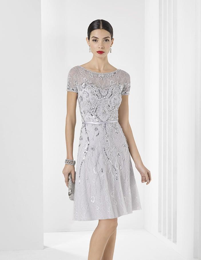 Закрытое вечернее платье серебристого цвета, украшенное стразами и дополненное поясом.