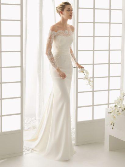 Утонченный образ создает прямое свадебное платье с фигурным портретным декольте, созданным кружевной тканью.  Кружево образует и длинные рукава.  На талии – широкий атласный пояс с причудливыми драпировками, украшенный на спинке пышным бутоном с тонкими лепестками.  Кроме того, спинка украшена вертикальной полосой декоративных пуговиц.  Небольшой шлейф облегающей фигуру юбки прекрасно завершает нежный и изысканный крой свадебного платья.