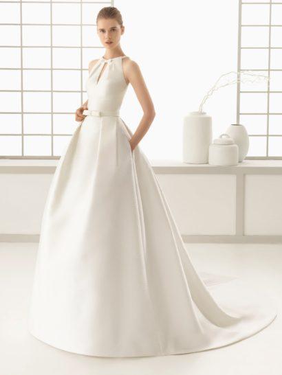 Великолепное свадебное платье из атласной ткани околдовывает изысканным дизайнерским решением. Американская пройма лифа дополнена округлым вырезом и небольшим V-образным декольте. На талии – утонченный узкий пояс с небольшим бантом. Спинка свадебного платья полностью закрыта, а пышную юбку со шлейфом стильно дополняют скрытые в легких вертикальных складках ткани карманы по бокам торжественного подола.