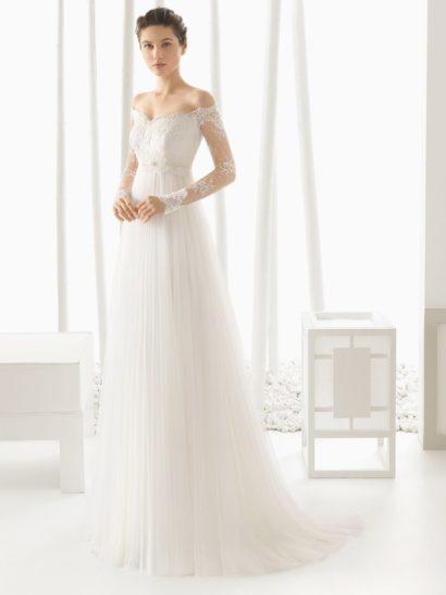 Потрясающее свадебное платье в ампирном стиле с очаровательным портретным декольте, дополненным облегающими кружевными рукавами с фигурными манжетами.  Завышенную линию талии помогает выделить широкая полоса кружева, а ниже спускается элегантная юбка, декорированная тонкими полосами плиссировки.  Сзади многослойный подол переходит в легкую романтичную волну небольшого шлейфа.