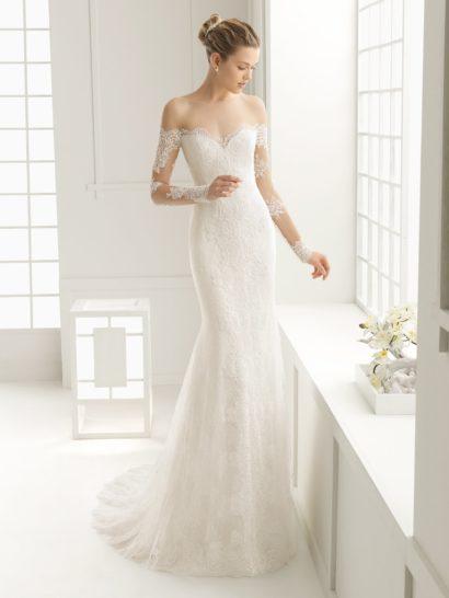 Облегающее свадебное платье с потрясающим портретным вырезом, украшенным кружевными аппликациями.  Дополнить соблазнительный верх помогают прозрачные облегающие рукава с кружевным декором.  На спинке – глубокий V-образный вырез с фигурным краем.  Юбку по всей длине декорирует кружево, а сзади ее дополняет и шлейф из нескольких слоев полупрозрачной ткани, спускающихся небольшими вертикальными складками.