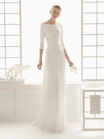 Оригинальное свадебное платье прямого кроя с широким портретным декольте, чувственно обнажающим плечи невесты.  Элегантные рукава длиной в три четверти, выполненные из плотной ткани, красиво дополняют вырез.  На талии – атласный пояс с горизонтальными драпировками.  Юбка с необычным оформлением верха подола выполнена из нескольких слоев ткани и украшена вертикальными полосами плиссировок по всей длине, включая шлейф.