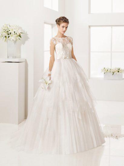 Необычное свадебное платье оригинально воплощает торжественный пышный крой. Объемную юбку покрывают слои полупрозрачных оборок разной длины, образующие выразительную фактуру.  Подчеркнуть линию талии помогает узкий атласный пояс с бантом, а выше корсет декорирован роскошной кружевной тканью с объемным рисунком.  Кружевная спинка гармонично вписывается в образ, как и длинные полупрозрачные рукава с аппликациями.