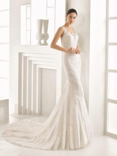 В этом великолепном свадебном платье удачно объединяются самые притягательные детали актуальных образов – облегающий, полный женственности силуэт «русалка» и деликатная отделка, выполненная из кружевной ткани с цветочным рисунком.  Элегантный V-образный вырез преображают фигурные аппликации на прозрачной основе, такая же отделка и на спинке.  Длинный шлейф из нескольких слоев ткани роскошным полукругом спускается сзади от уровня коленей.