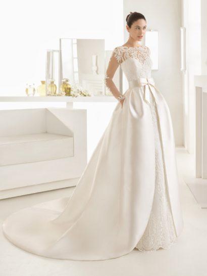 Сногсшибательное свадебное платье-трансформер сделает образ невесты особенно незабываемым.  Роскошная атласная верхняя юбка пышного кроя с широким поясом, украшенным бантом, может быть снята, чтобы преобразить силуэт из торжественного в более притягательный.  Нижняя юбка кроя «русалка» по всей длине покрыта кружевом, прекрасно сочетающимся с ее соблазнительным характером.  Длинные рукава и кружевная спинка красиво завершают изысканный образ.
