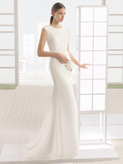 Безупречное свадебное платье прямого силуэта, выполненное из лаконичного атласа, создано для невесты с изысканным вкусом, предпочитающей дополнительным деталям совершенство кроя.  Округлый вырез без отделки акцентирует женственные линии шеи, широкие бретели помогают усилить это впечатление.  Спинка закрыта, что делает образ еще более впечатляющим и стильным. Дополнить прямую юбку помогает небольшой шлейф, легкими волнами спускающийся сзади.