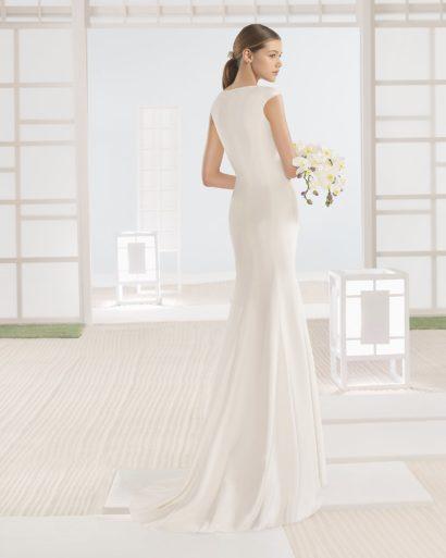 Изысканное свадебное платье прямого кроя с закрытым верхом и небольшим шлейфом.