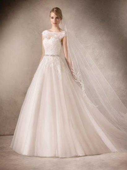 Романтичное свадебное платье элегантного кроя «принцесса» создает атмосферу нежности многослойной воздушной юбкой, спускающейся пышными вертикальными волнами и украшенной кружевом лишь по верхней части подола.  Хрупкую талию невесты помогает очертить узкий сверкающий пояс, покрытый серебристым бисером.  Корсет с лифом в форме сердечка покрыт тонкой кружевной тканью, на спинке она обрамляет глубокое декольте округлой формы.  Свадебные платьяLa Sposa 2017эксклюзивно представлены в салоне Виктория