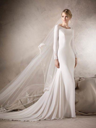 Стильное свадебное платье из атласной ткани придает своей лаконичностью облегающему силуэту «русалка» драматичное очарование.  Длинные рукава украшены кружевными манжетами, верх платья декорирован лишь вертикальными швами по корсету.  Сдержанный округлый вырез декольте прекрасно сочетается с соблазнительной кружевной спинкой, украшенной декоративными пуговицами.  Подчеркнуто длинный шлейф служит прекрасной заключительной деталью.  Свадебные платьяLa Sposa 2017эксклюзивно представлены в салоне Виктория