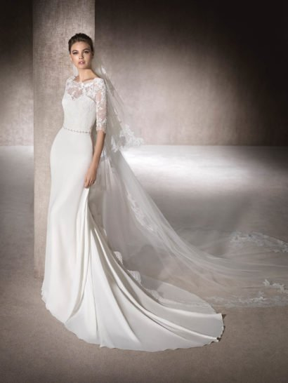 Изящный прямой силуэт свадебного платья задает тон всему настроению этого элегантного образа.  Торжественный характер помогает подчеркнуть шлейф, а верх выполнен в очень женственном стиле, с кружевной отделкой, фигурным вырезом и полупрозрачными рукавами длиной до локтя.  На талии располагается узкий пояс с блестящей бисерной отделкой.  Спинка украшена глубоким округлым декольте, обрамленным кружевной тканью.