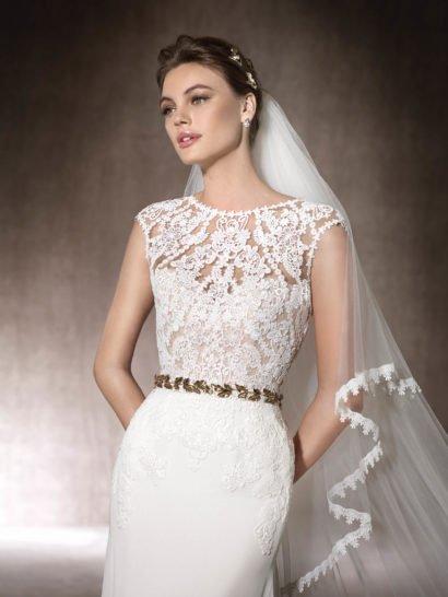 Прямое свадебное платье с кружевным верхом, открытым декольте на спинке и шлейфом.