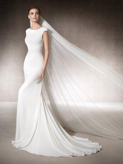 Утонченное пляжное свадебное платье облегающего кроя «русалка» безупречно подчеркивает фигуру и настраивает своей изысканной лаконичностью на особенный торжественный лад.  Изящный округлый вырез декольте с широкими бретелями смотрится очень стильно и женственно.  Сзади – потрясающий глубокий вырез, открывающий спинку, под которым располагается вертикальный ряд декоративных пуговиц, а еще ниже простирается нежный и элегантный шлейф.