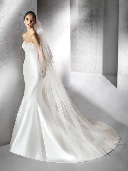 Роскошное свадебное платье из глянцевого атласа безупречно обрисовывает изгибы фигуры беспроигрышной комбинацией открытого лифа в форме сердечка и женственного силуэта «русалка».  Край линии декольте украшен деликатной вышивкой белым бисером.  Лаконичную атласную юбку спереди украшают лишь декоративные вертикальные швы, а сзади она переходит в потрясающий полукруг шлейфа.