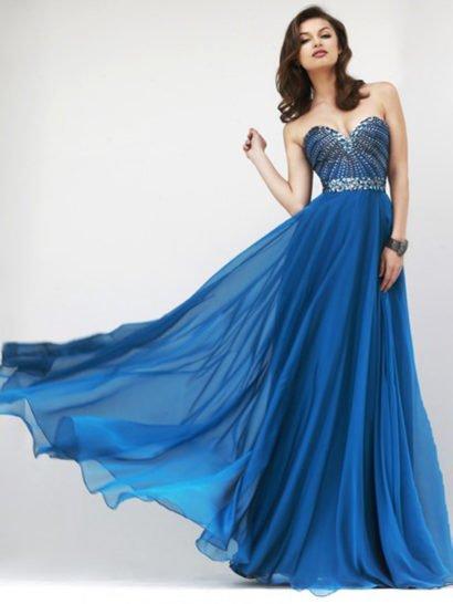 Открытое вечернее платье элегантно акцентирует область декольте классическим лифом в форме сердца, очертания которого подчеркивает отделка крупными стразами в тон синей ткани. Великолепный декор из стразов располагается по линии талии широкой полосой, выполняя функцию элегантного пояса. Юбка прямого кроя покрыта несколькими слоями легкого полупрозрачного шифона, который красиво струится по фигуре.