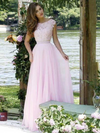 Романтичное выпускное платье с элегантной длинной юбкой очаровывает нежным розовым оттенком ткани.  Розовое и кружево, украшающее закрытый верх с широкими бретелями и фигурным округлым вырезом.  На спинке – глубокий чувственный вырез V-образной формы.  Талию выделяет узкий пояс с отделкой из блестящего бисера в тон, бисер деликатно украшает небольшими акцентами также верх вечернего платья.