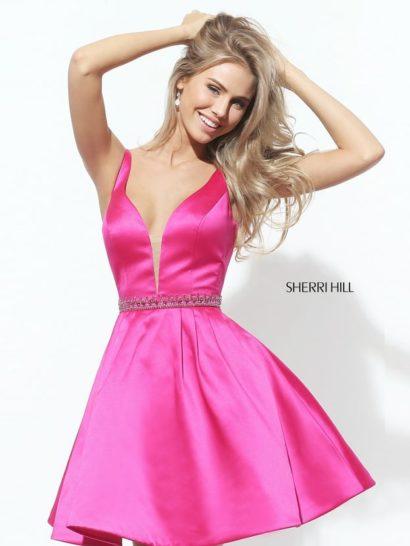 Изысканное и лаконичное выпускное платье идеально подойдет для утонченной девушки, которой нравятся образы с несколькими эффектными акцентами. В данном образе акцентом служит глубокое V-образное декольте с вставкой в тон кожи. Привлекает внимание и насыщенный розовый оттенок плотной атласной ткани. На талии – изящный сверкающий пояс с бисерной вышивкой. Юбка длиной до середины бедра украшена вертикальными складками по верху подола.