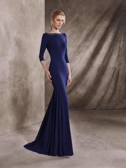 Утонченное вечернее платье идеально подойдет для образа свидетельницы на свадебной церемонии. Глубокий синий оттенок великолепно сочетается с облегающим кроем, рукавами длиной в три четверти и элегантным вырезом «лодочка». Спинка вечернего платья открыта впечатляющим V-образным вырезом декольте, спускающимся почти до линии талии. Края декольте спереди и выреза сзади украшены сверкающим декором из стразов.