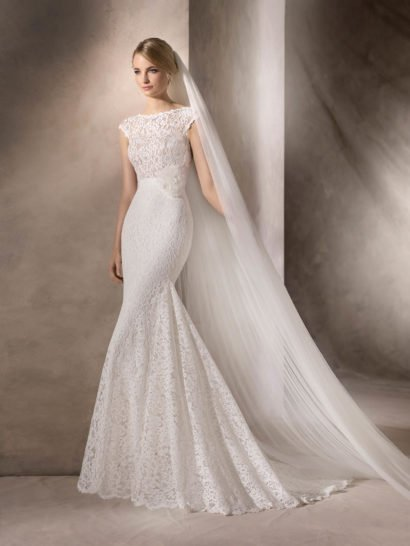 Изысканное свадебное платье облегающего кроя «русалка» выполнено из плотной кружевной ткани на элегантной белой подкладке.  Соблазнительный силуэт изящно дополняет вырез «лодочкой», обрамленный кружевной тканью.  На спинке – округлое декольте, укрытое кружевной вставкой с рядом декоративных пуговиц.  При желании, свадебное платье можно преобразить элегантным широким поясом с объемным цветочным бутоном или акцентом из сияющих стразов.