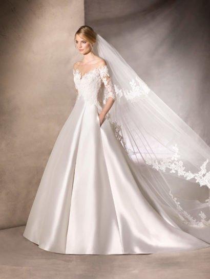 Элегантное свадебное платье кроя «принцесса» с умопомрачительной юбкой из шелка микадо, оформленной вертикальными складками, длинным шлейфом сзади и скрытыми карманами по верху подола. Корсет изящно объединяется с юбкой и подчеркивает фигуру женственным вырезом в форме сердечка, дополняют декольте рукава длиной до локтя. Верх оформлен тюлем, кружевом и вышивкой из бисера, придающей образу деликатный блеск.