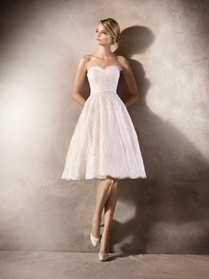 Очаровательное свадебное платье по всей длине покрыто слоем кружевной ткани, создающей романтичное настроение. Пышная юбка длиной до колена прекрасно поддерживает его, как и изящный корсет с лифом в форме сердца, очерчивающий фигуру. Легкий оттенок слоновой кости, созданный подкладкой, делает платье особенно оригинальным, а деликатная бисерная вышивка по кружеву создает атмосферу торжественности.