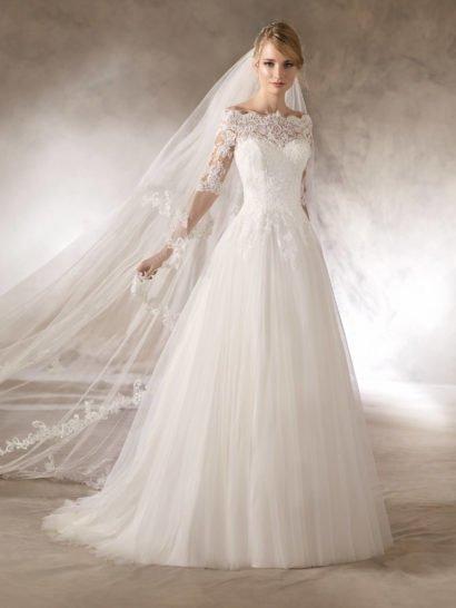 Деликатное свадебное платье с классическим силуэтом «принцесса» притягивает внимание многослойной юбкой из тюля. Верх с выразительным портретным декольте и кружевными рукавами длиной до локтя оформлен бисерной вышивкой. Кружевом украшен и вырез на спинке свадебного платья. Кроме того, сзади платье украшает элегантный многослойный шлейф, спускающийся вертикальными волнами легкой ткани.