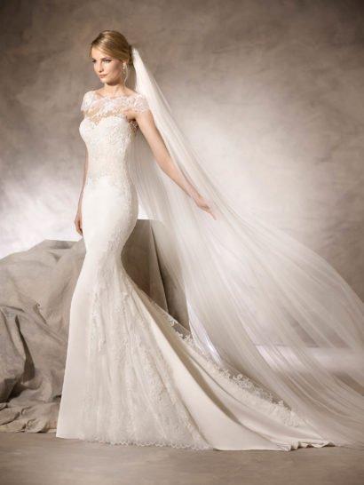 Прекрасное свадебное платье, подчеркивающее фигуру кроем «русалка», выполнено из изысканного атласа, дополненного тюлем, шантильским кружевом, вышивкой и гипюром. Короткие рукава и фигурный вырез лодочкой смотрятся утонченно и нежно, на спинке – более глубокое декольте, покрытое кружевной тканью, подчеркивающей деликатность обнаженной кожи. Завершает образ полукруг шлейфа из атласа с кружевным верхом.
