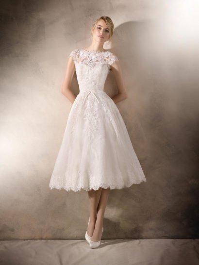 Деликатное и романтичное свадебное платье длиной до колена создает необычный, стильный образ. Верх и пышную многослойную юбку нежно оформляют кружево и гипюровая ткань, дополненные сверкающей вышивкой. Фигурный вырез в форме лодочки и узкий пояс с трогательным бантиком спереди придают образу женственное и беззаботное настроение. На спинке – выразительное декольте.