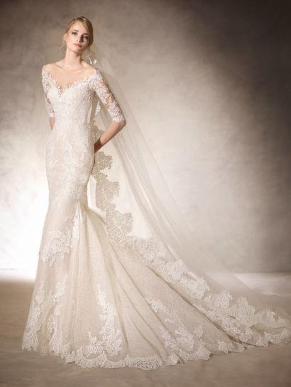 Впечатляющее свадебное платье облегающего кроя «русалка» смотрится невероятно соблазнительно благодаря комбинации силуэта и выреза декольте в форме сердечка.  Рукава длиной до локтя выполнены из нежного кружева.  Кружевом, гипюром и вышивкой из стразов платье украшено по всей длине, включая роскошный многослойный шлейф, вертикальными волнами спускающийся сзади от уровня коленей.