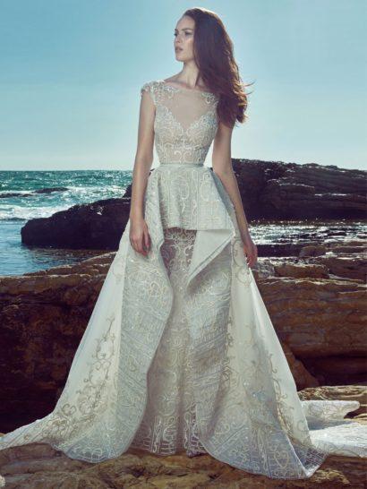 Оригинальное свадебное платье пышного силуэта привлекает внимание необычной верхней юбкой из фактурной плотной ткани, создающей объемную баску на уровне талии и оттеняющую кружевную полупрозрачную юбку прямого кроя снизу.  Элегантный облегающий корсет с лифом в форме сердечка украшен кружевной тканью и дополнен полупрозрачной вставкой над вырезом, создающей женственное декольте лодочкой.    Свадебные платья Zuhair Muradэксклюзивно представлены в салоне Виктория  Примерка платьевZuhair Murad—платная