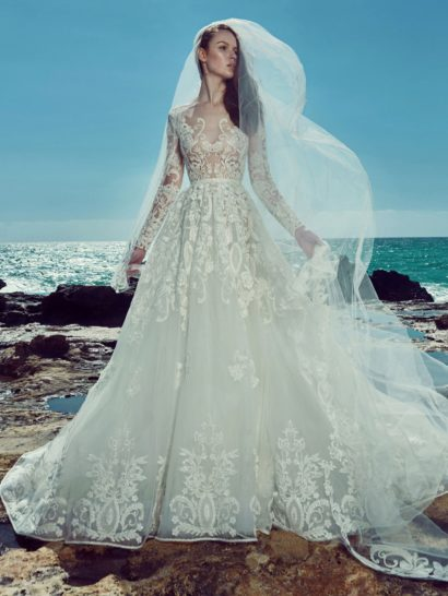 В невероятно роскошном свадебном платье органично объединяются современные и классические детали.  Классической основой служит пышная многослойная юбка со шлейфом, задающая тон всему свадебному платью.  Смелой и актуальной деталью является полупрозрачный верх с кружевным декором, фигурным декольте и длинными облегающими рукавами.  Кружевной узор украшает и низ подола, придавая ему еще большую притягательность.    Свадебные платья Zuhair Muradэксклюзивно представлены в салоне Виктория  Примерка платьев Zuhair Murad—платная