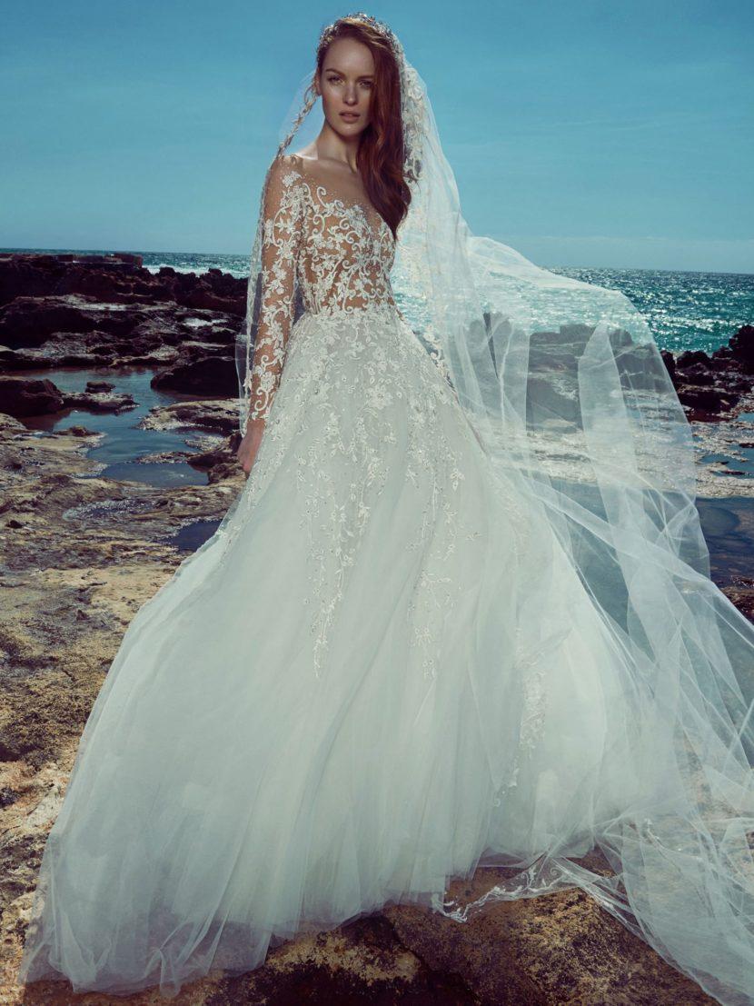 Кружевное свадебное платье с полупрозрачным верхом и многослойной юбкой.