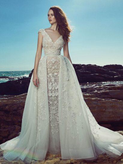 Романтичное свадебное платье элегантного оттенка слоновой кости очаровывает фактурной вышивкой с цветочным мотивом, украшающей как верх с глубоким декольте с вырезом V-образной формы, так и юбку сложного кроя.  Подчеркнуть торжественность момента помогает пышность низа платья – у него две юбки. Нижняя юбка полупрозрачная и нежная, а верхняя – более пышная и спускается сзади и по бокам, образуя эффектный воздушный шлейф.    Свадебные платья Zuhair Muradэксклюзивно представлены в салоне Виктория  Примерка платьев Zuhair Murad—платная