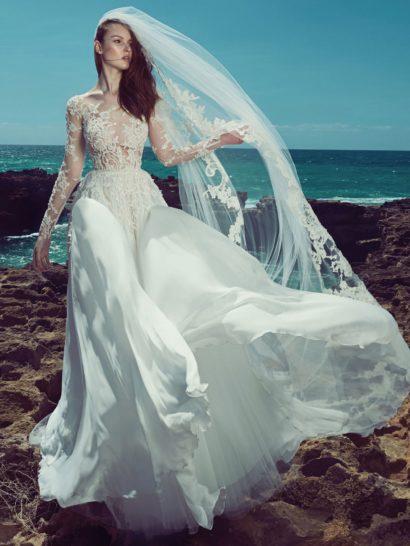 Изысканное свадебное платье прямого кроя приковывает взгляды полупрозрачным верхом с фактурной кружевной отделкой.  Длинные рукава привносят в образ некоторую сдержанность, которая великолепно смотрится в сочетании с чувственным характером тонкой ткани.  Юбка необычного кроя создана из нескольких слоев ткани разной фактуры, мягко струящихся по фигуре и элегантно очерчивающих ее максимально удачным образом.  Свадебные платья Zuhair Muradэксклюзивно представлены в салоне Виктория