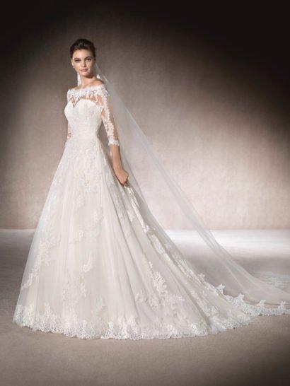 Элегантное свадебное платье «принцесса» создано из легкого тюля с романтичными кружевными аппликациями, гипюровой тканью и вышивкой бисером. Фигурное портретное декольте, обнажающее плечи, и рукава длиной чуть ниже локтя смотрятся по-настоящему очаровательно и изящно. Глубокий вырез декольте на спинке оформлен полупрозрачной кружевной тканью, подчеркивающей чувственность обнаженной кожи.