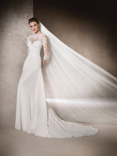 Незабываемо красивое свадебное платье с лаконичной юбкой, облегающей бедра и переходящей сзади в неповторимый длинный шлейф из тонкой ткани, струящейся роскошными волнами. Открытый корсет с женственным лифом в форме сердечка украшено тюлем, кружевной тканью и бисерной вышивкой. Отделка закрывает вырез, украшает открытую спинку и создает стильные облегающие рукава длиной в три четверти с фигурным краем.