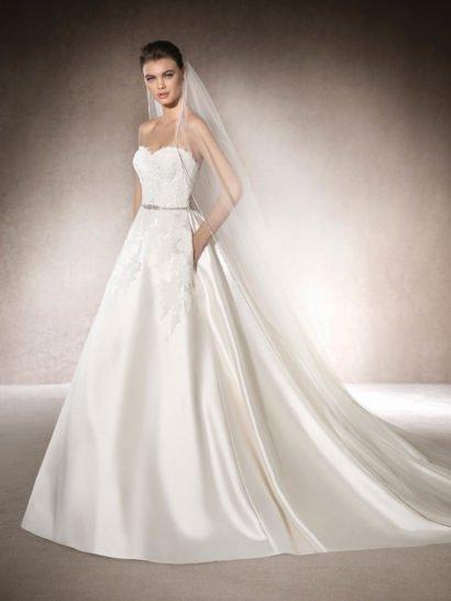 Открытое свадебное платье А-силуэта околдовывает великолепной юбкой из шелка микадо. Мягкий блеск шелковой ткани становится дополнительным украшением роскошного длинного шлейфа, простирающегося сзади. Открытый корсет с лифом в форме сердца покрыт кружевными аппликациями, гипюровой тканью и бисерной вышивкой, кроме того, талию очерчивает узкий пояс, полностью покрытый сверкающим бисером.